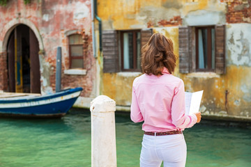 Young woman in venice, italy looking at map. rear view