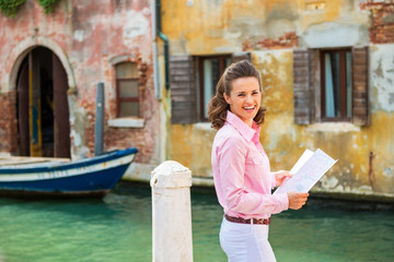 Portrait of happy young woman with map in venice, italy