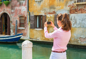 Young woman in venice, italy taking photo. rear view