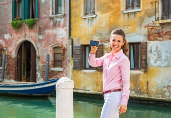 Happy young woman showing photo camera while in venice, italy