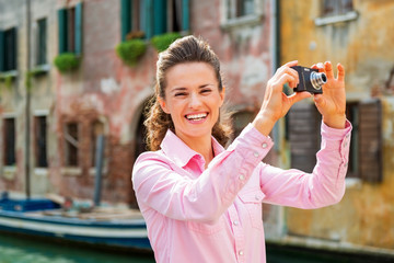 Smiling young woman taking photo in venice, italy