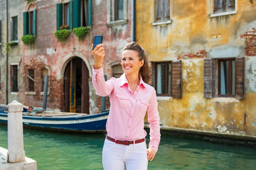 Happy young woman making selfie in venice, italy