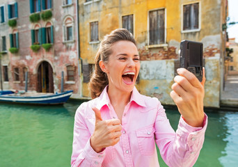 Happy young woman showing thumbs up and making selfie in venice
