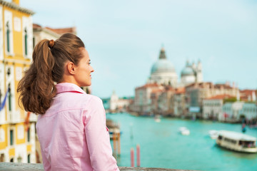 Woman looking into distance while standing on bridge in venice
