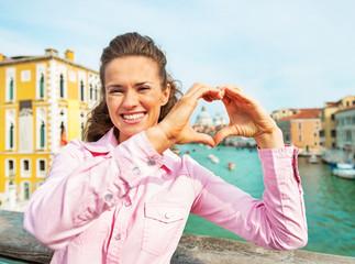 Woman showing heart shaped hands framing san maria della salute