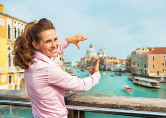 Woman framing with hands while standing on bridge in venice