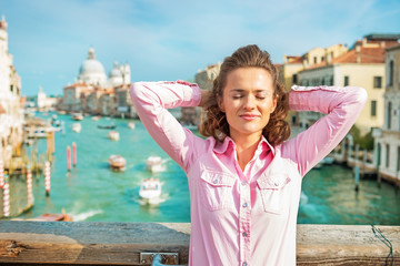 Relaxed  woman standing on bridge with grand canal view