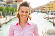 Portrait of smiling young woman standing on bridge in venice