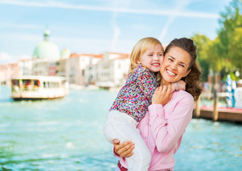 Portrait of mother and baby hugging on grand canal embankment