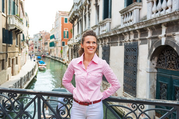 Happy young woman standing on bridge in venice, italy