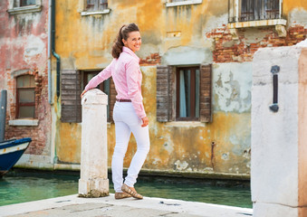 Happy young woman standing on street in venice, italy