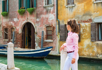 Young woman looking on canal in venice, italy. rear view