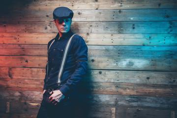 Retro 30s fashion man wearing blue cap, shirt, braces and jeans