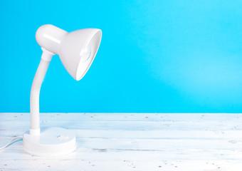 White lamp on white wood desk, blue background