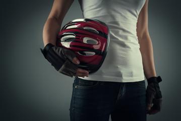 Cycling woman holding biking protective helmet