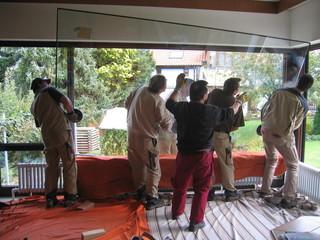 Sechs Handwerker beim Einbauen einer schweren Fensterscheibe