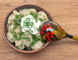 Russian dumplings in a clay bowl with sour cream and dill on a w