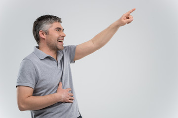 Man pointing up and laughing on grey background