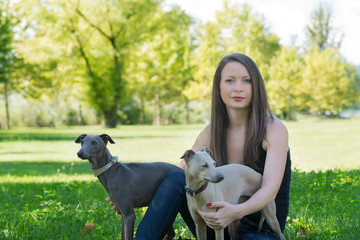 Sitting girl  with two greyhounds in the park