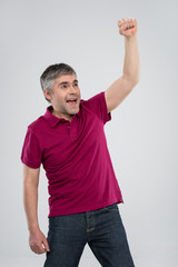 Casual man winning and celebrating over white background.