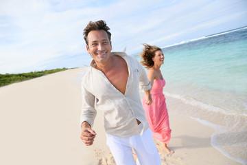 Couple having fun running on a caribbean beach