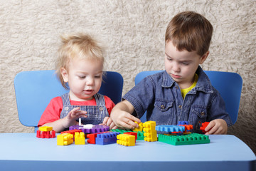 two brothers are building blocks of sitting at the table