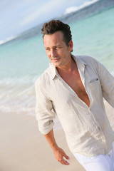 Handsome 40-year-old man walking on beach