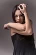 Portrait of beautiful female model on grey background.