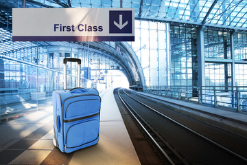First Class. Blue suitcase at the railway station