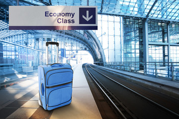 Economy Class. Blue suitcase at the railway station