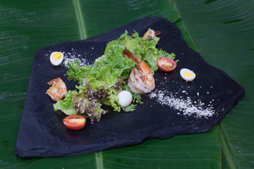 Fried shrimp with lettuce on a black stone instead of plate