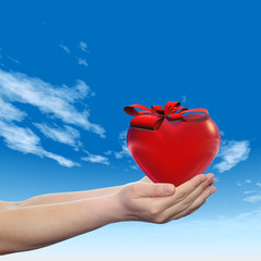 3D conceptual heart with a ribbon held in hands
