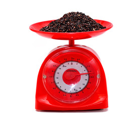 weight measurement balanceand Black Rice isolated white backgrou