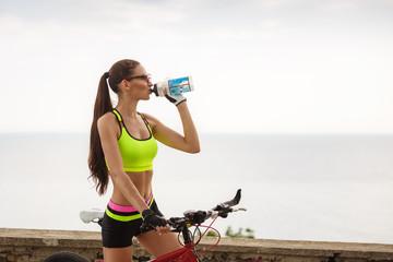Beautiful woman refreshing drinking water at the bike