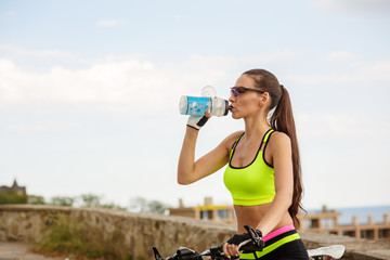 Beautiful woman refreshing drinking water at the bike