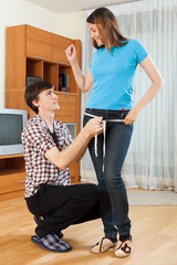 Guy measuring girlfriend with measuring tape