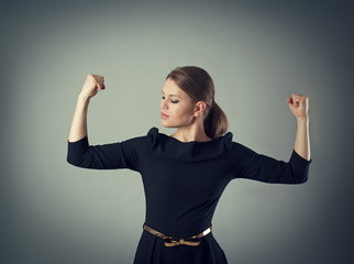 Powerful business woman. Young female looking at muscled arms