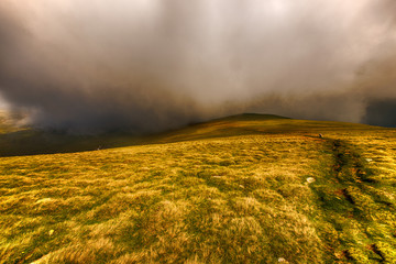 Landscape with Fagaras mountains in Romania and clouds amongst t
