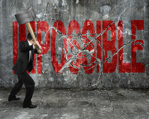 businessman using sledgehammer cracking red impossible word brok