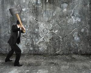 businessman using sledgehammer cracking wall broken on concrete