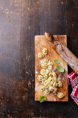 Homemade raw Tortellini and basil leaves on dark wooden backgrou