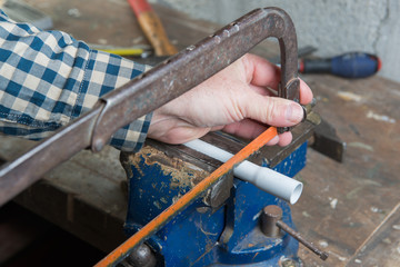 man cut PVC pipe with a handsaw