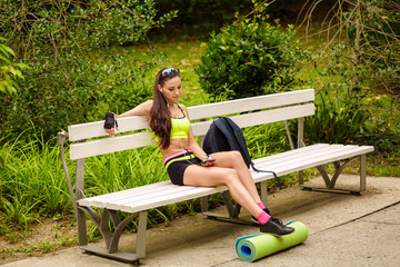 Young woman enjoying the music sitting on the bench in sport wea