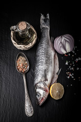 Fresh sea fish lying on dark background with spices. Vertical