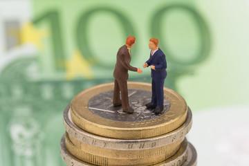Geschäftsmänner auf Münzenstapel