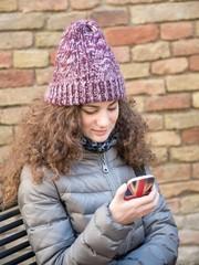 Ragazza messaggia dal telefono seduta sulla panchina in inverno