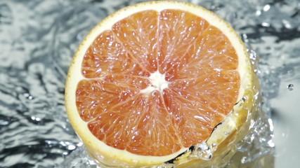 Sliced citrus fruit splashing into water