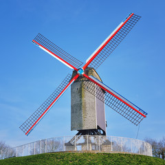 Windmill in Bruges with blue sky at the background