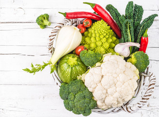 Fresh vegetables in basket on white wood rustic background