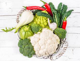 Vegetables in basket on wood background.